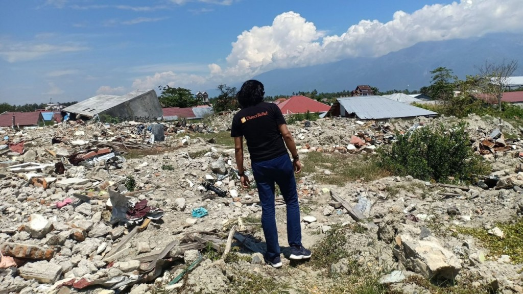 Direct Relief Intern Aprisal Malae surveys ruins in his native Central Sulawesi. (Aprisal Malale for Direct Relief)